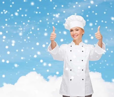 thumps up: christmas, cooking, profession, gesture and people concept - smiling female chef showing thumps up over blue snowy sky and cloud  Stock Photo