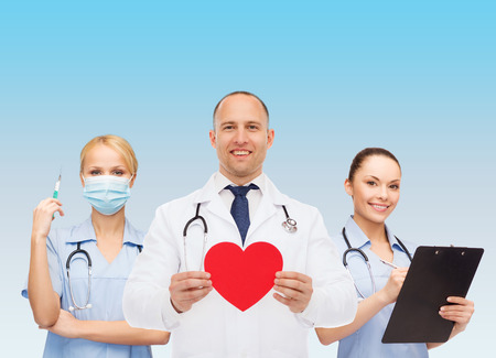 medics: medicine, profession, teamwork and healthcare concept - international group of smiling medics or doctors holding red paper heart shape clipboard and stethoscopes over blue background