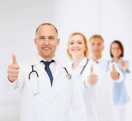 approvement: profession, teamwork, gesture and medicine concept - smiling male doctor with stethoscope in coat over group of medics showing thumbs up