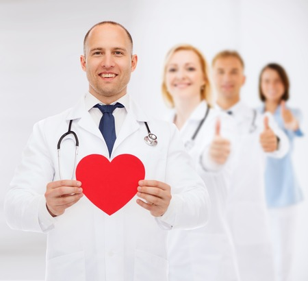 medics: medicine, charity, gesture and healthcare concept - smiling doctor with red heart and stethoscope over group of medics showing thumbs up