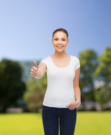 approvement: advertising, summer vacation, gesture and people concept - smiling young woman in blank white t-shirt showing thumbs up over park