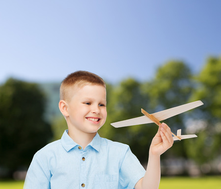 dreams, future, hobby, nature and childhood concept - smiling little boy holding wooden airplane model in his hand over park  photo