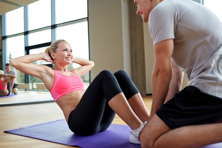 ups: fitness, sport, training, gym and lifestyle concept - woman with personal trainer doing sit ups in gym