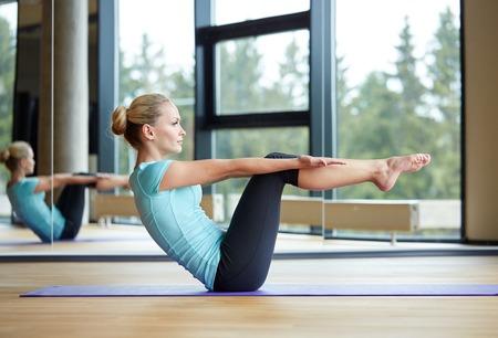 haciendo ejercicio: fitness, deporte, formación y concepto de la gente - sonriente mujer haciendo ejercicios abdominales sobre colchoneta en el gimnasio Foto de archivo