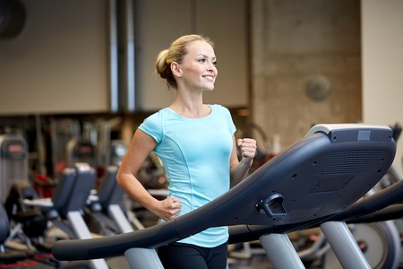woman working out: sport, fitness, lifestyle, technology and people concept - smiling woman exercising on treadmill in gym