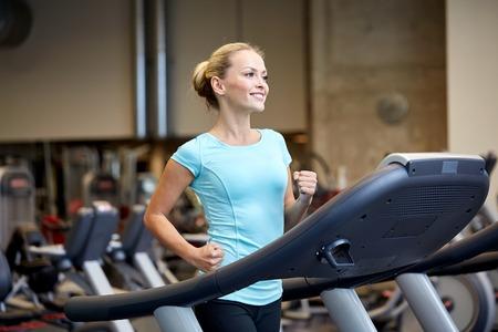 Sport, forme physique, mode de vie, la technologie et les gens notion - femme exerçant sur tapis roulant dans le gymnase en souriant Banque d'images - 34563455