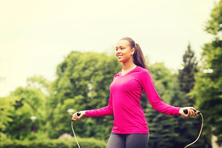 woman rope: fitness, sport, training, park and lifestyle concept - smiling african american woman exercising with jump-rope outdoors