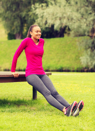 fitness, sport, training, park and lifestyle concept - smiling african american woman doing push-ups on bench outdoors photo