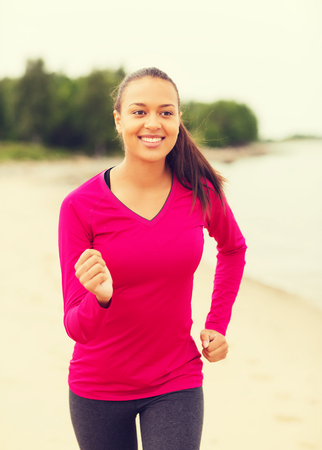fitness, sport, training and lifestyle concept - smiling african american woman running on track outdoors photo