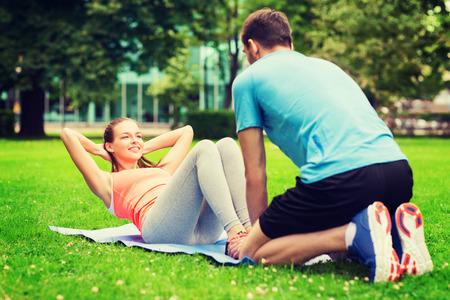 thể dục, thể thao, đào tạo, làm việc theo nhóm và lối sống khái niệm - mỉm cười với người phụ nữ huấn luyện viên cá nhân làm bài tập trên mat ngoài trời