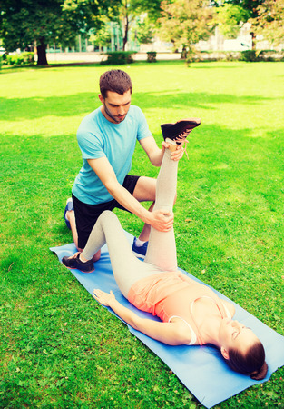 fitness, sport, training and lifestyle concept - serious couple stretching on mat outdoors photo