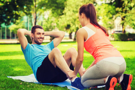 outdoors: fitness, sport, training, teamwork and lifestyle concept - smiling man with personal trainer doing exercises on mat outdoors