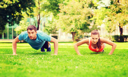 work hard: fitness, sport, training and lifestyle concept - couple doing push-ups outdoors