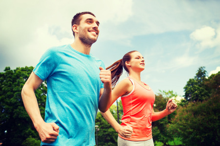 athletic: fitness, sport, friendship and lifestyle concept - smiling couple running outdoors