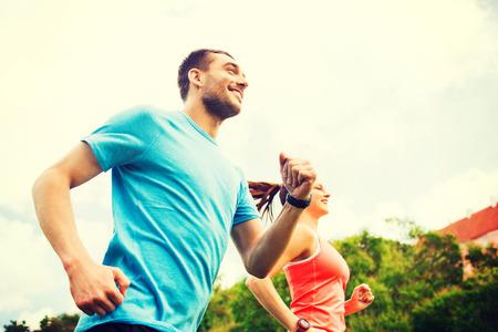 фитнес: фитнес, спорт, дружба и образ жизни концепция - улыбается пара работает на открытом воздухе