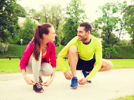fitness, sport, friendship and lifestyle concept - smiling couple tying shoelaces outdoors