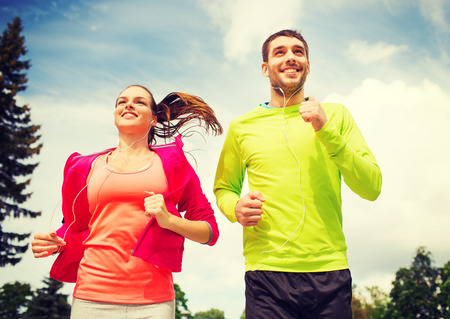 fitness, sport, friendship and lifestyle concept - smiling couple with earphones running outdoors 스톡 콘텐츠