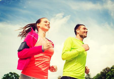 фитнес: фитнес, спорт, дружба и образ жизни концепция - улыбается пара с наушники, работает на открытом воздухе