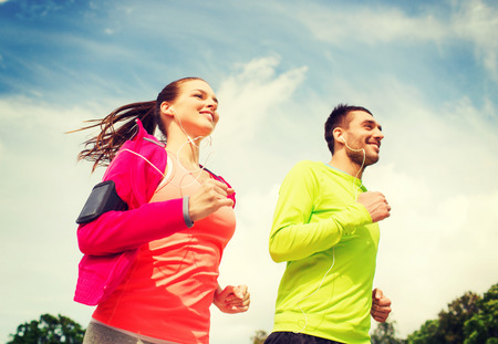 fitness, sport, friendship and lifestyle concept - smiling couple with earphones running outdoors Stockfoto