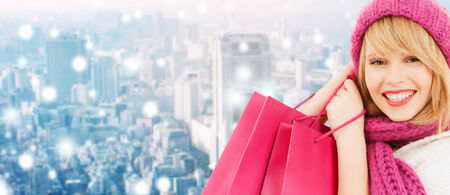 young girl smiling: happiness, winter holidays, christmas and people concept - smiling young woman in hat and scarf with pink shopping bags ove snowy city background