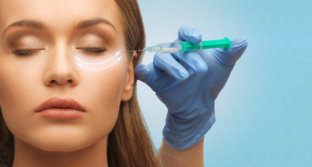 medicine, plastic surgery, beauty, health and people concept - close up of hand in medical glove with syringe making injection to beautiful woman face over blue background photo