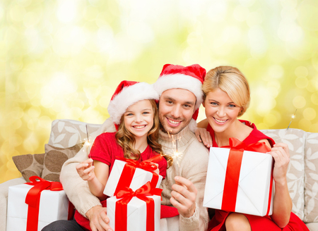 family, christmas, xmas, happiness and people concept - smiling family in santa helper hats with many gift boxes and bengal lights photo