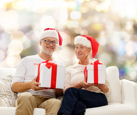 family, holidays, christmas, age and people concept - happy senior couple in santa helper hats with gift boxes over lights background photo