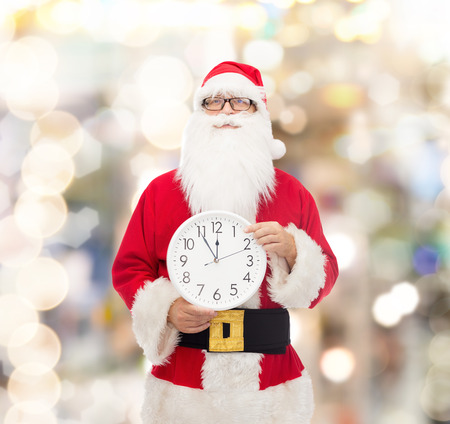 twelve month old: christmas, holidays and people concept - man in costume of santa claus with clock showing twelve pointing finger over lights background