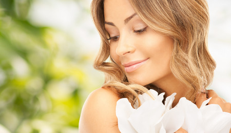 bare shoulders: beauty, people and health concept - beautiful young woman with flowers and bare shoulders over green background Stock Photo