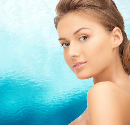 bare women: beauty, people and health concept - beautiful young woman with bare shoulders over blue water background Stock Photo