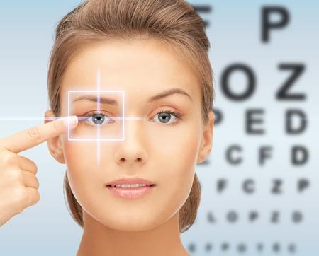 ojo humano: la medicina, el control de la vista, la correcci�n con l�ser, la gente y el concepto de salud - mujer hermosa joven que se�ala el dedo en el ojo y sobre fondo azul con la carta de ojo Foto de archivo