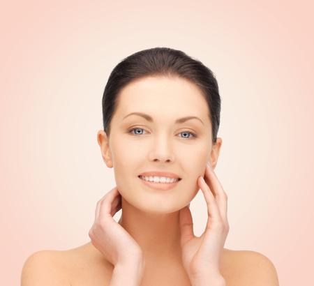 Beauté, personnes et concept de santé - belle jeune femme touchant son visage sur fond rose Banque d'images
