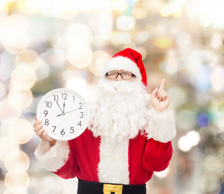 hurry up: christmas, holidays and people concept - man in costume of santa claus with clock showing twelve pointing finger up over lights background