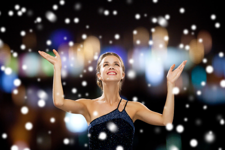 people, happiness, holidays and christmas concept - smiling woman raising hands and looking up over snowy night city lights background photo
