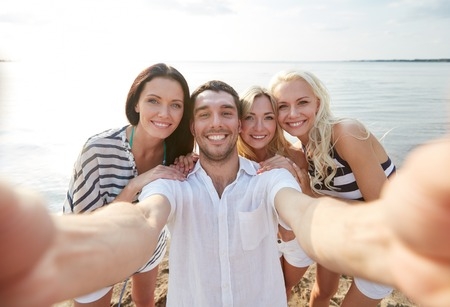 summer, sea, tourism, technology and people concept - group of smiling friends with camera on beach photographing and taking selfie