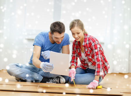 repair, building, family, people and home concept - smiling couple measuring parquet plank on floor photo
