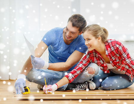redesign: repair, building, family, people and home concept - smiling couple measuring parquet plank on floor