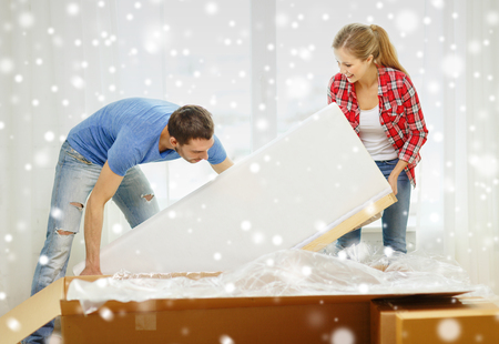 moving box: repair, moving in and people concept - smiling couple opening big cardboard box with sofa at home Stock Photo