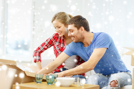 moving box: repair, moving in and people concept - smiling couple opening , unpacking cardboard box with dishes at home