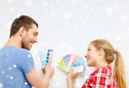 repair, interior design, building, renovation and people concept - smiling couple selecting color from samples at home photo