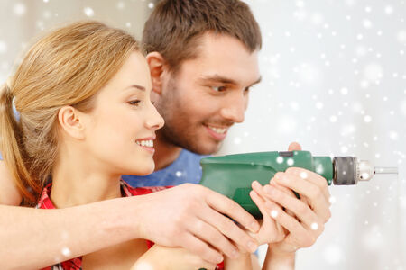 repair, interior design, building, renovation and family concept - smiling couple drilling hole in wall at home photo