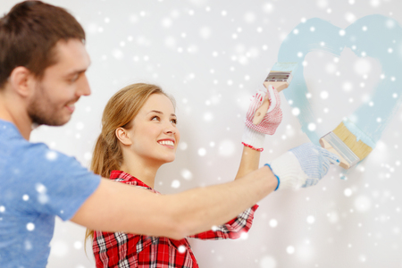 a small painting: repair, building, love, people and home concept - smiling couple painting small heart on wall at home Stock Photo