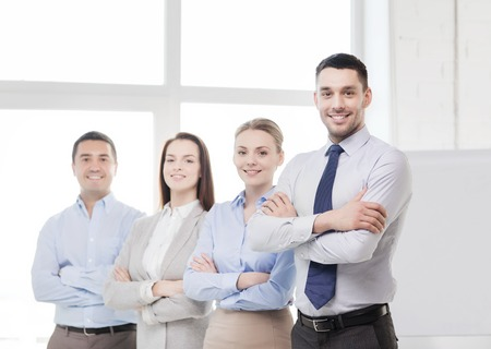mani incrociate: business and office concept - smiling handsome businessman with crossed hands and team in office