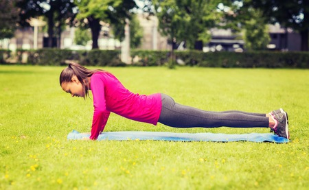 fitness, sport, training, park and lifestyle concept - smiling woman doing doing push-ups on mat outdoors photo