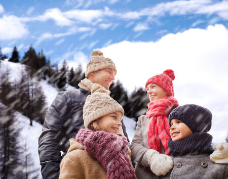 family, childhood, season and people concept - happy family in winter clothes over snowy mountains background photo
