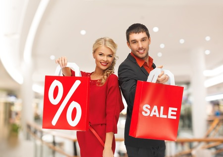 consumerism: sale, consumerism and people concept - happy young couple with red shopping bags in mall Stock Photo