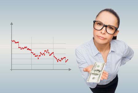 moneyless: business, bankruptcy, people and banking concept - smiling businesswoman in eyeglasses with dollar cash money over gray background and forex graph going down Stock Photo