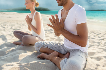 meditation man: fitness, sport, yoga, people and lifestyle concept - happy couple sitting in lotus pose on beach