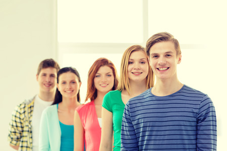 High school student: education and school concept - group of smiling students with teenage boy in front