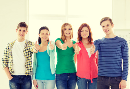 passed: education and school concept - group of smiling students at school showing thumbs up Stock Photo